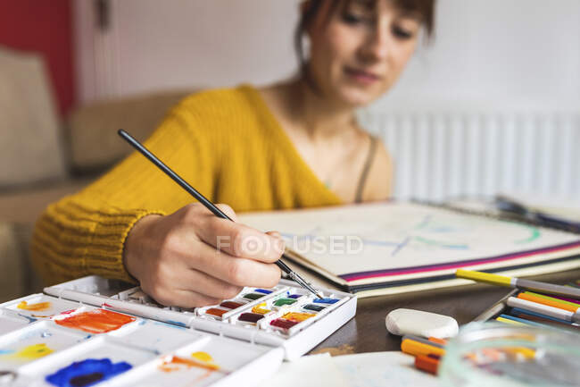 Hand of woman painting with watercolours — Stock Photo