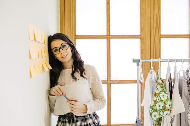 Retrato de mujer joven en la oficina apoyada contra una pared con notas adhesivas - foto de stock