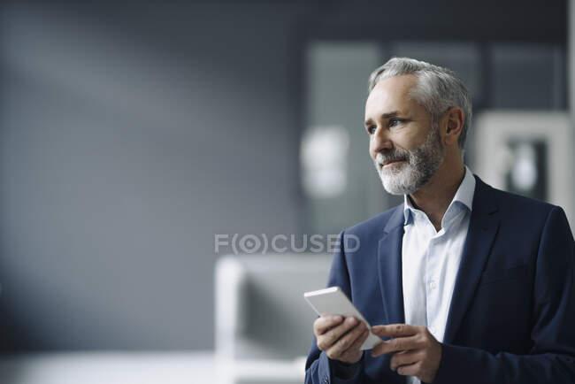 Портрет дорослого бізнесмена з смартфоном, що дивиться на відстань. — стокове фото