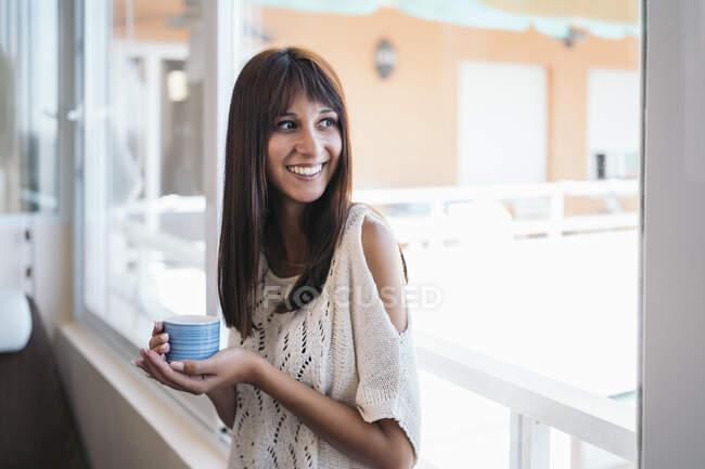 Retrato de una joven sonriente con taza de café cerca de la ventana en casa - foto de stock