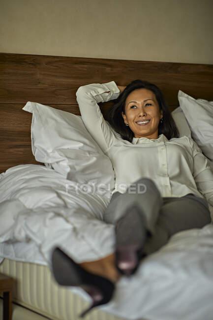 Sorridente donna d'affari sdraiata sul letto in camera d'albergo — Foto stock