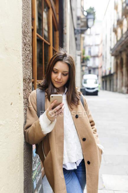 Giovane donna che controlla il suo telefono in città, Barcellona, Spagna — Foto stock