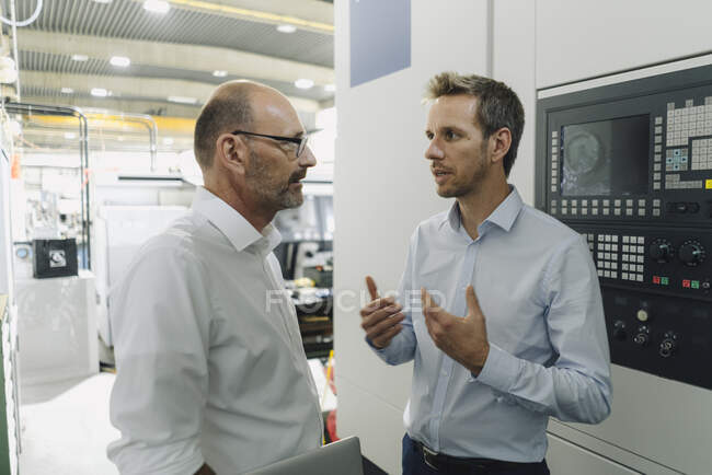Two men talking in a factory — Stock Photo