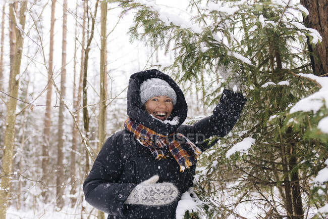 Portrait of laughing woman in winter forest enjoying snowfall — Stock Photo