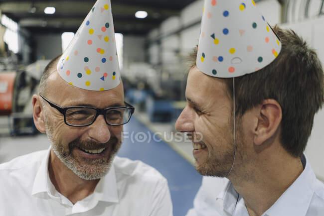 Портрет двох щасливих бізнесменів у вечірніх капелюхах на заводі. — стокове фото