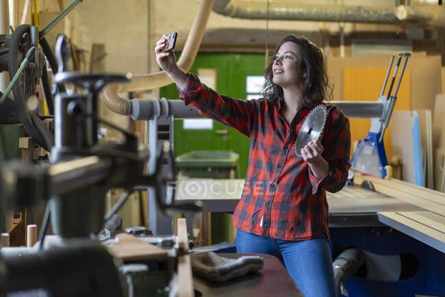 Handwerkerin mit Sägeblatt macht Selfie in ihrer Werkstatt — Stockfoto