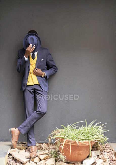 Молодий бізнесмен у старомодному костюмі закриває обличчя капелюхом. — стокове фото