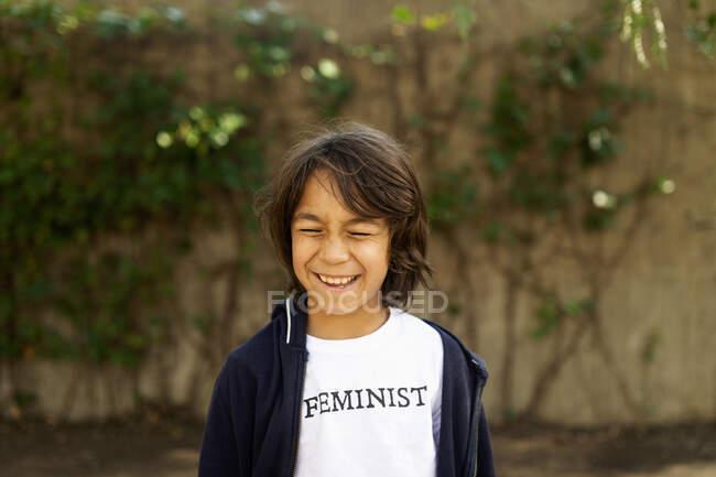 Lachender Junge, der mit T-Shirt-Aufdruck auf der Straße steht und sagt: Feminist — Stockfoto