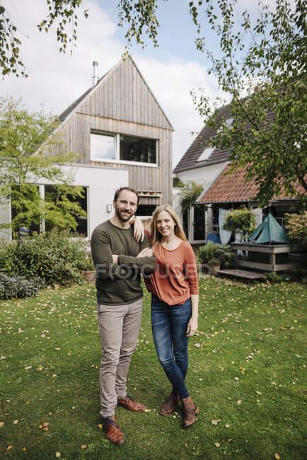 Горді господарі дому стоять у своєму саду. — стокове фото