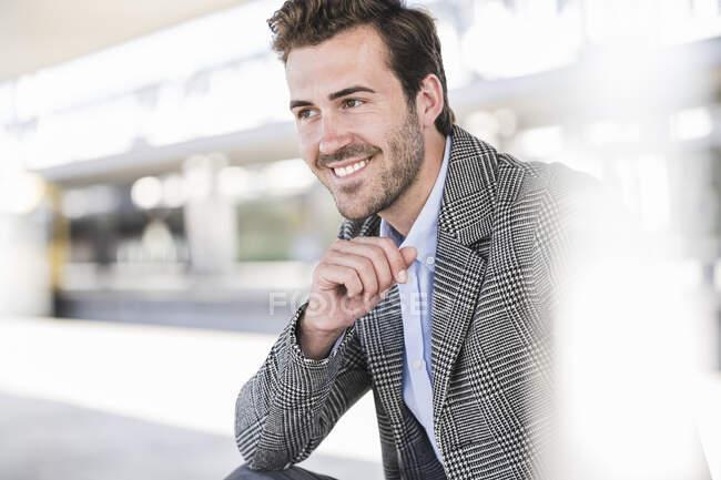 Ritratto di giovane uomo d'affari sorridente alla stazione ferroviaria — Foto stock