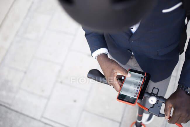 Вигляд людини з штовхаючим скутером за допомогою смартфона — стокове фото