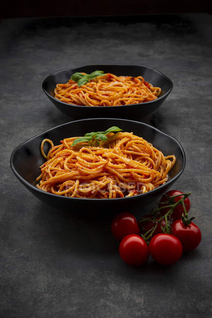 Bowls of spaghetti with basil andParmesan — Stock Photo