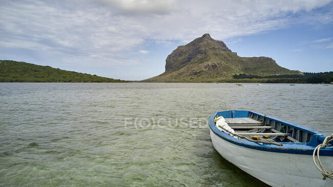 Mauritius, Empty rowboat floating in water with Le Morne Brabant peninsula in background — Stock Photo