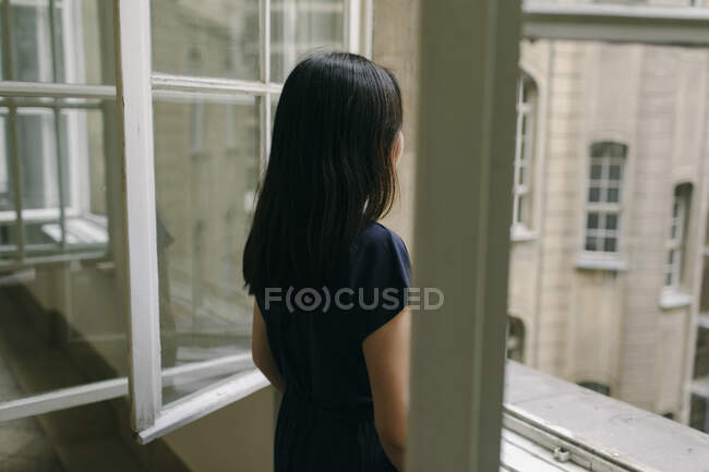 Vista trasera de la mujer mirando por la ventana - foto de stock