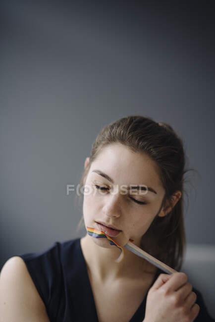 Retrato de una joven sacando cinta adhesiva de su boca - foto de stock
