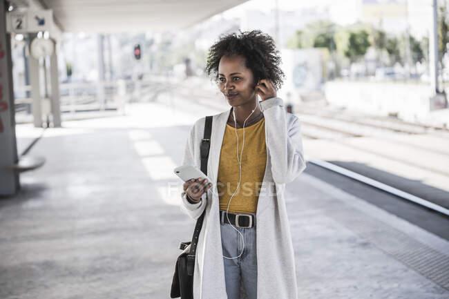 Молодая женщина с сотовым телефоном и наушниками на вокзале — стоковое фото