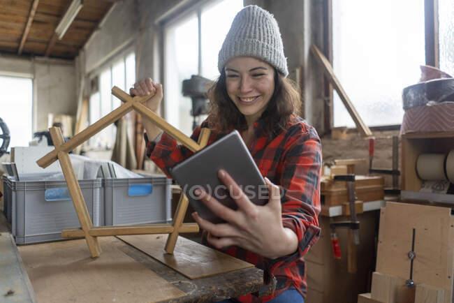 Lächelnde Tischlerin hält Tablet und Werkstück in ihrer Werkstatt — Stockfoto