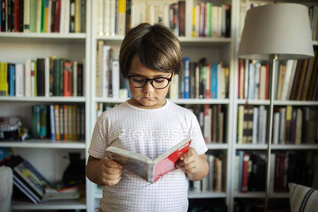 Portrait of serious boy with glasses standing in front of book shelves reading a comic — Stock Photo