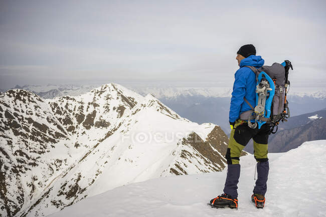 Man standing on the peak of a snowy mountain, Lombardy, Valtellina, Italy — Stock Photo