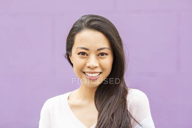 Porträt einer glücklichen Frau mit langen braunen Haaren vor violettem Hintergrund — Stockfoto