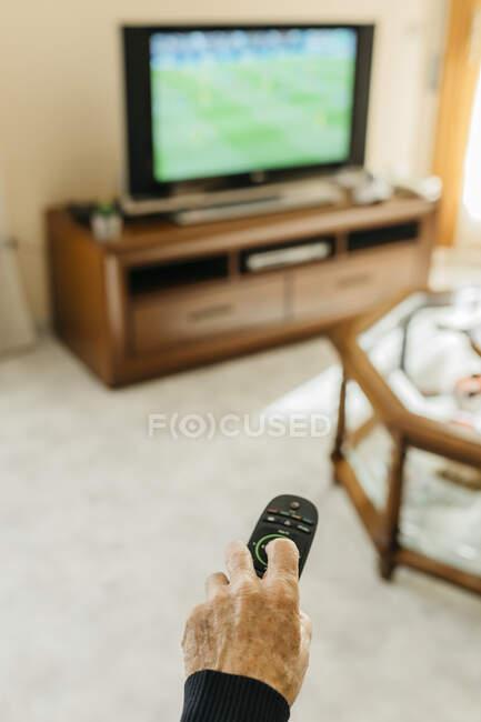Hand of senior man using remote control — Stock Photo