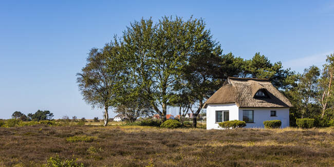 Germany, Mecklenburg-Western Pomerania, Small rustic house on sunny day — Stock Photo