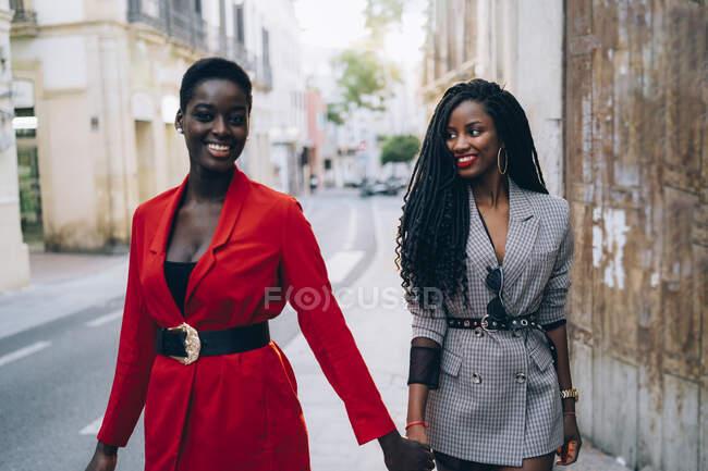 Dos mujeres tomadas de la mano en la ciudad - foto de stock