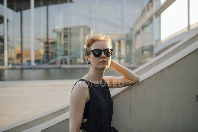 Elegant red-haired woman with sunglasses in the city, portrait — Stock Photo