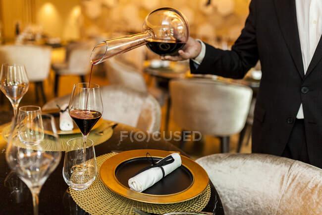 Camarero vertiendo vino de decantador en vidrio en restaurante de lujo - foto de stock