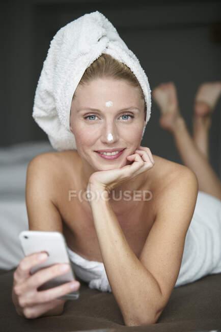 Портрет красивой женщины с головой, завернутой в полотенце, держащей смартфон на кровати — стоковое фото