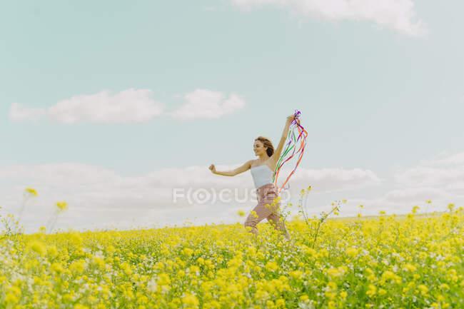 Щаслива молода жінка рухається з барвистими стрічками на квітковому лузі навесні. — стокове фото