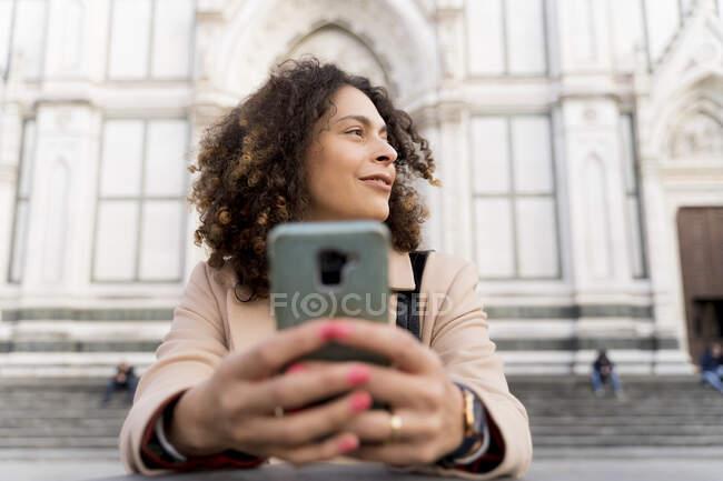 Mujer con smartphone en la iglesia de Santa Croce, Florencia, Italia - foto de stock