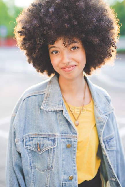 Retrato de mujer joven con peinado afro en la ciudad - foto de stock