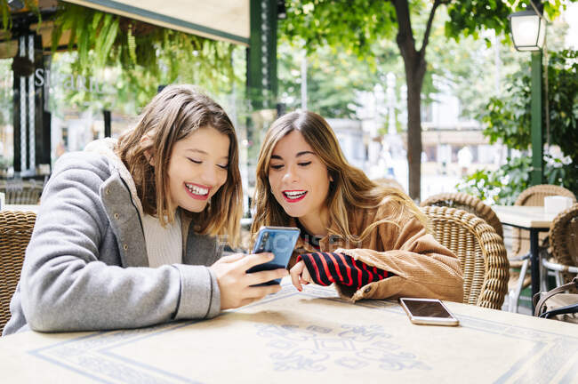 Dos jóvenes felices con teléfono inteligente en un café al aire libre - foto de stock