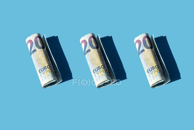 Banconote da 20 euro arrotolate su sfondo blu — Foto stock