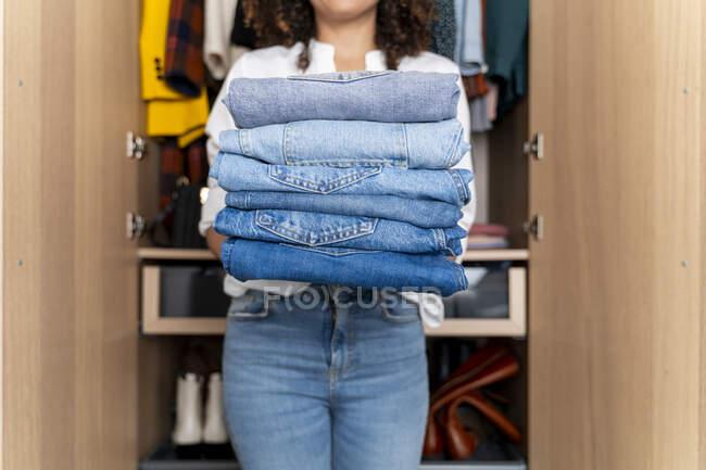 Mulher em pé na frente do guarda-roupa segurando pilha de jeans azuis — Fotografia de Stock