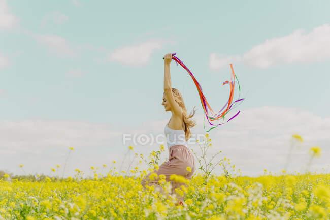 Счастливая молодая женщина движется с красочными лентами на цветочном лугу весной — стоковое фото