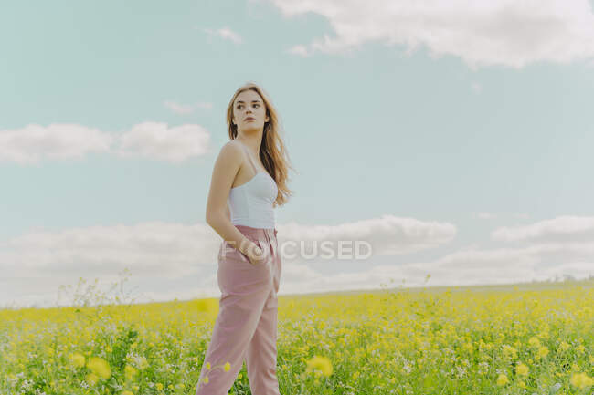 Young woman standing in a flower meadow in spring — стокове фото