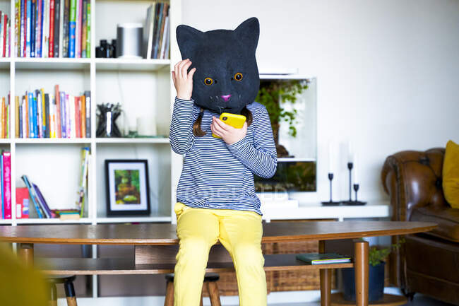 Little girl, wearing cat mask, using smartphone — Stock Photo
