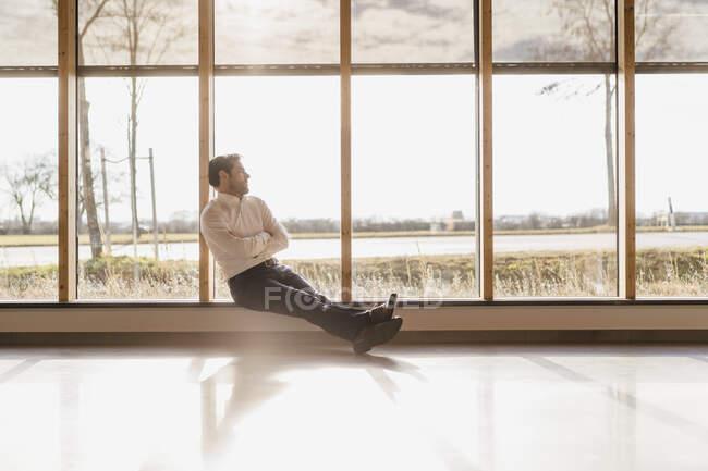 Бизнесмен, сидящий у окна в офисе открытой планировки — стоковое фото