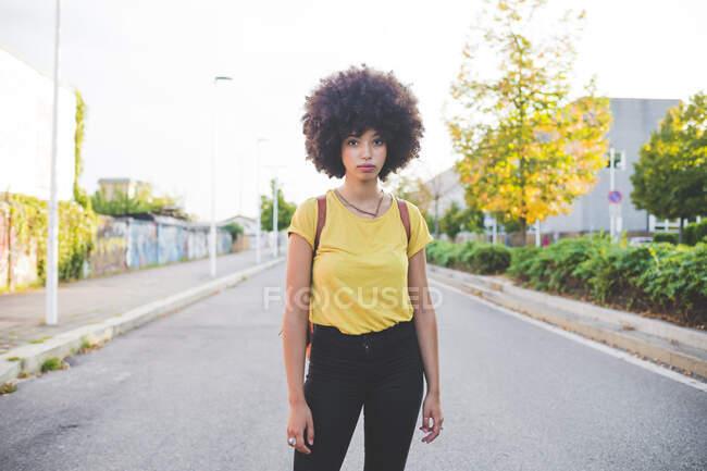 Портрет молодої жінки з волоссям африканського кольору стоїть на вулиці в місті. — стокове фото