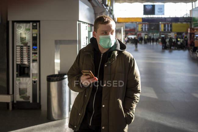 Joven con máscara facial en la estación de tren de la ciudad, sosteniendo el teléfono inteligente - foto de stock