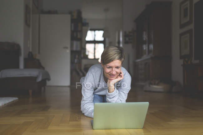 Mature woman working from home, using laptop, kneeling on floor — Stock Photo