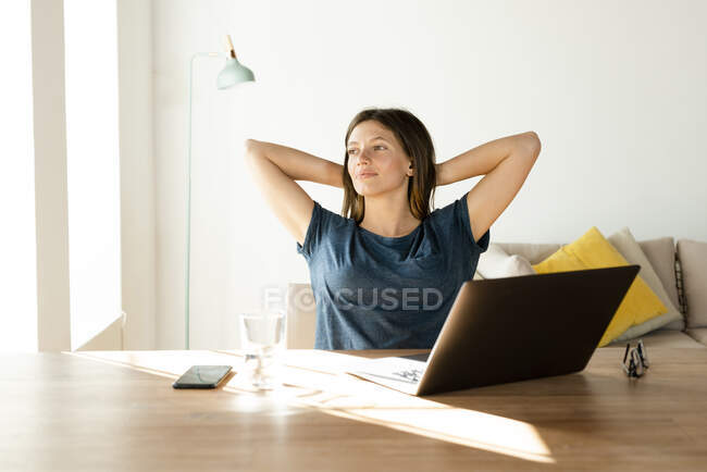 Content young woman at home having a break from working at laptop in home office — Stock Photo