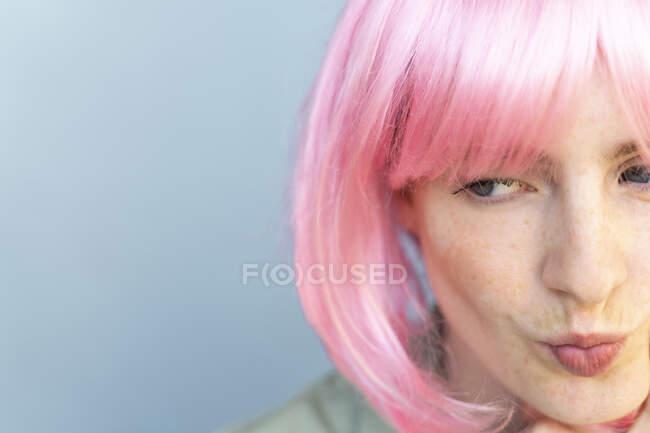Retrato de una mujer joven con peluca rosa haciendo pucheros en la boca - foto de stock