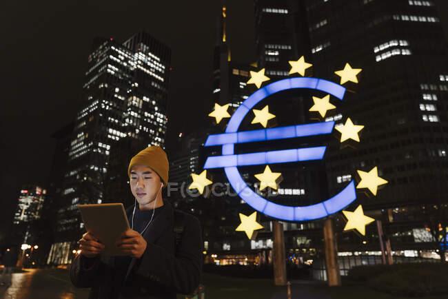 Uomo che usa tablet in città di notte con la Banca centrale europea sullo sfondo, Francoforte, Germania — Foto stock