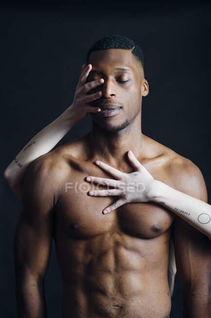 As mãos da mulher tocando o corpo do namorado no estúdio — Fotografia de Stock