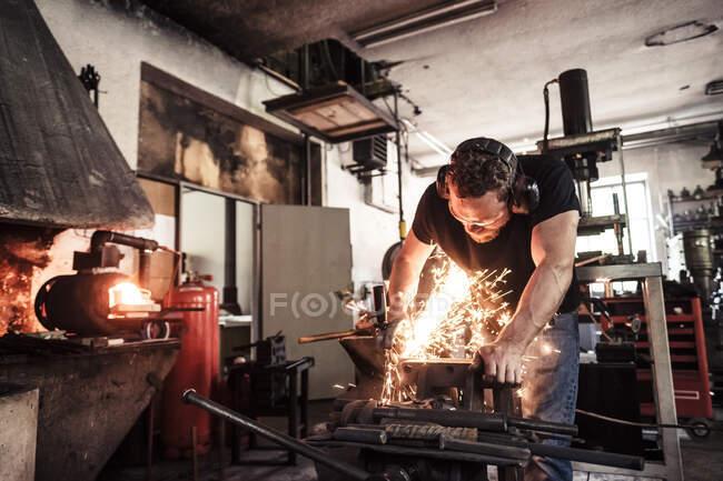 Knife maker cutting steel workpiece — Stock Photo