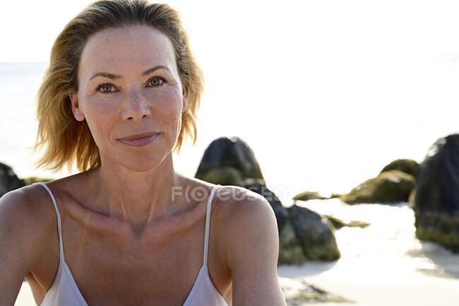 Портрет жінки на пляжі, що дивиться на камеру. — стокове фото