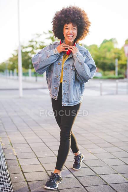 Retrato de una joven feliz con peinado afro en la ciudad - foto de stock